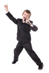 cute little boy in business suit with microphone singing and dancing isolated on white background