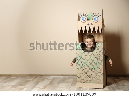 Cute little boy in cardboard costume of dinosaur near color wall. Space for text