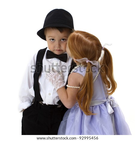 cute little boy in hat and tie scowling as he is kissed by a darling little red head girl