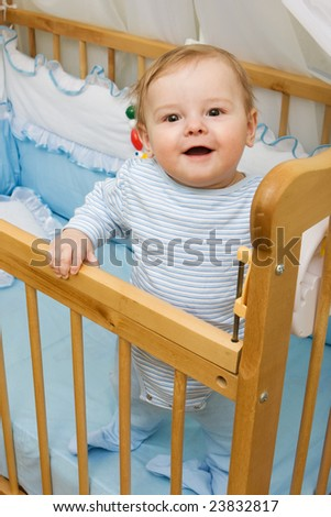 Cute little boy in his crib smiling