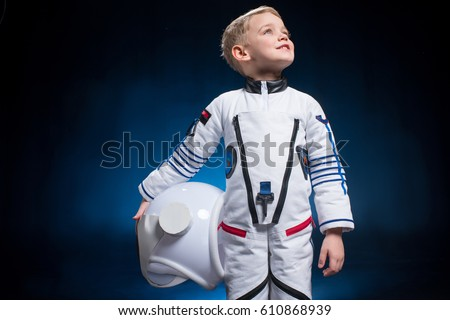 Cute little boy in space suit holding helmet and looking at distance