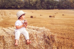Cute little boy in straw hat eating bread sitting on hay stack in harvested yellow wheat field. Summer lifestyle. Child nutrition. Rural scene. Copy space