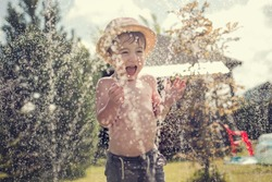 Cute little boy in straw hat is laughing and having fun running under water spraying hose. Image with selective focus and toning