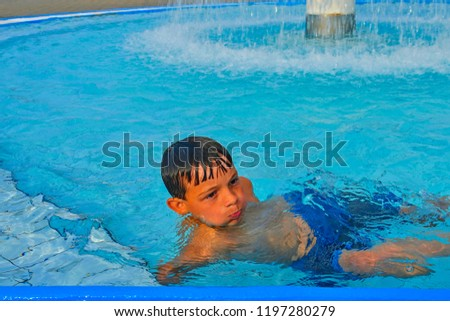 Cute little boy in the public swimming pool. Portrait of little cute boy in the swimming pool. Sunny summer day. Summer and happy chilhood concept.  #1197280279