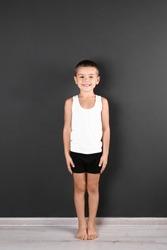 Cute little boy in underwear near dark wall