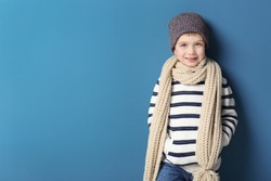 Cute little boy in warm clothing on color background. Ready for winter vacation