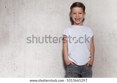 Cute little boy in white T-shirt posing in front of grunge concrete wall. Portrait of fashionable male child. Smiling boy posing, gray wall on background. Concept of children style and fashion.