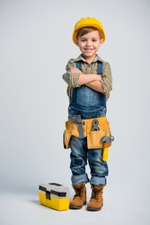 Cute little boy in yellow hard hat and tool belt smiling at camera  isolated on grey
