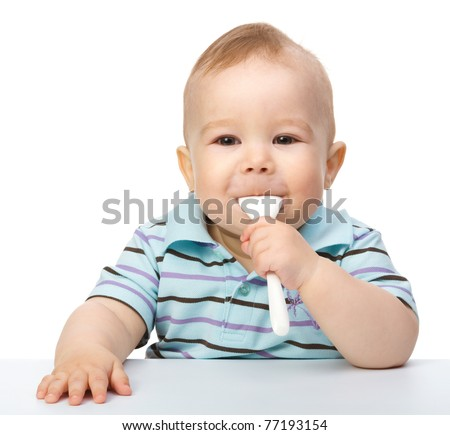 Cute little boy is biting a spoon while sitting at table, isolated over white