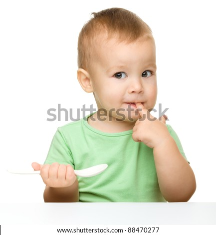 Cute little boy is biting his finger while holding a spoon and sitting at table, isolated over white