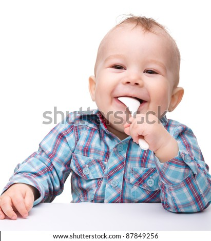 Cute little boy is biting spoon while sitting at table, isolated over white