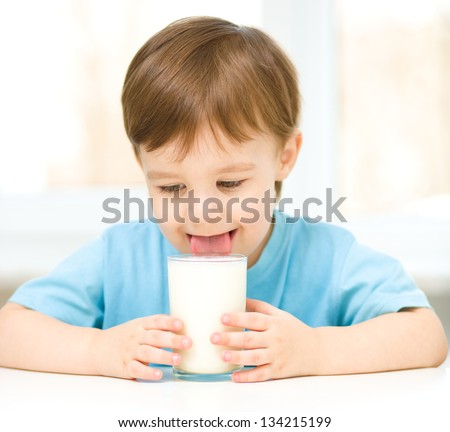 Cute little boy is dipping his tongue in the glass of milk