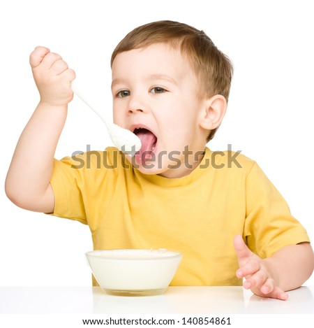Cute little boy is eating cottage cheese using spoon, isolated over white