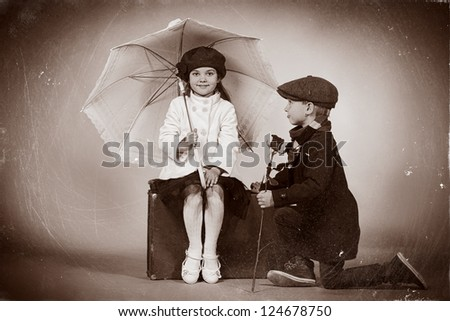 Cute little boy is giving a rose to the charming little lady. Retro style.
