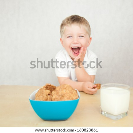 Cute little boy is having a breakfast. Child eating cookies and drinking milk. - stock photo