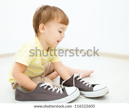 Cute little boy is playing with big sneakers while sitting on the floor