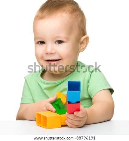 Cute little boy is playing with building bricks while sitting at the table, isolated over white