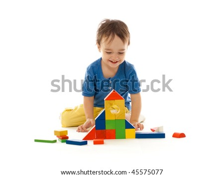 Cute little boy is playing with colorful building wooden blocks isolated on white