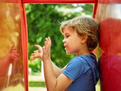 Cute little boy is playing with his reflection in children's slide on the playground. Conducts a conversation with an imaginary friend