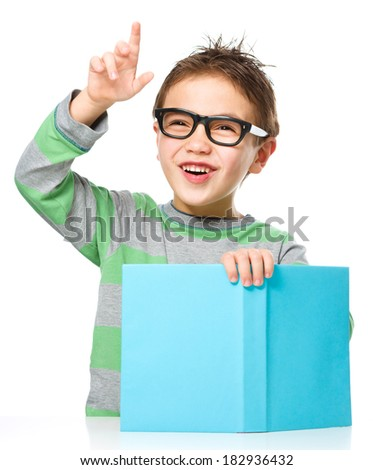 Cute little boy is reading a book while wearing glasses and explaining something gesturing with hands, isolated over white