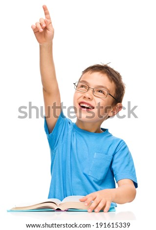 Cute little boy is reading a book while wearing glasses and pointing up using his index finger, isolated over white