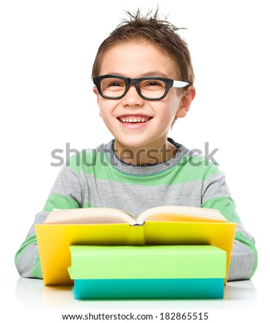 Cute little boy is reading a book while wearing glasses, isolated over white