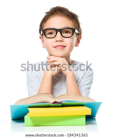 Cute little boy is reading a book while wearing glasses supporting his head with hands, isolated over white