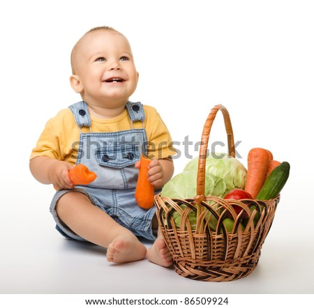 Cute little boy is sitting on the floor with basket full of vegetables, isolated over white