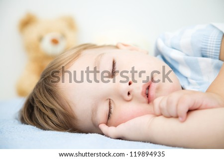 Cute little boy is sleeping in front of his teddy bear