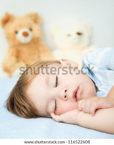 Cute little boy is sleeping on a white pillow