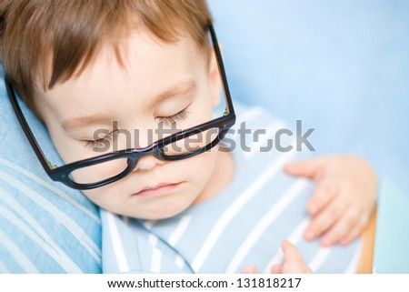 Cute little boy is sleeping while wearing glasses and put off his book