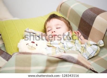 Cute little boy is sleeping with his teddy bear