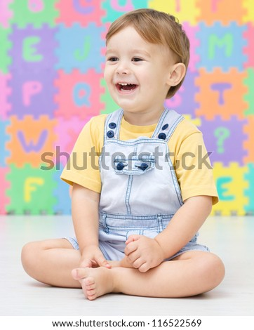 Cute little boy is smiling while sitting on the floor