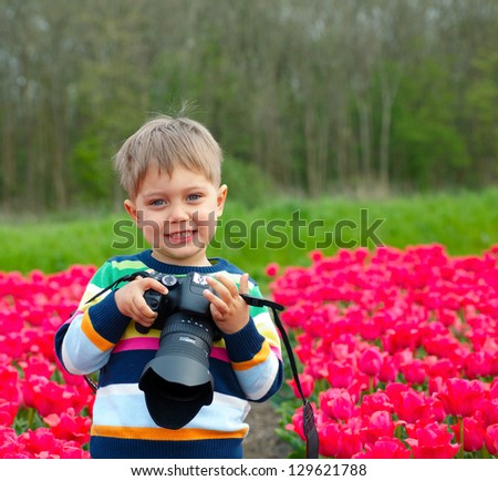 Cute little boy is taking pictures in field with tulips in Holland