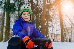 Cute little boy, kid in winter clothes walking under the snow. Child enjoy a sleigh ride around woods in park. Sun glare effect.