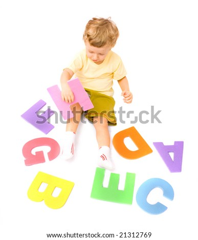 Cute little boy learning alphabet playing with letters. Isolated over white - stock photo