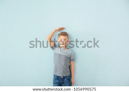 Cute little boy measuring height near color wall