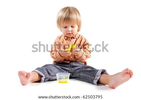 Cute little boy molding plasticine, isolated on white background