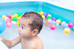 Cute little boy 17 month with water and plastic ball toy in plastic pool. happy family in summer hollidays concept.