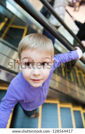 Cute little boy on escalator in mall