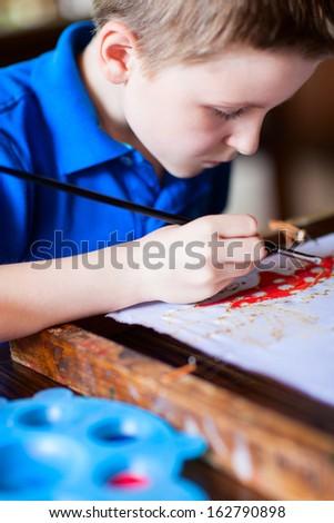 Cute little boy painting a batik