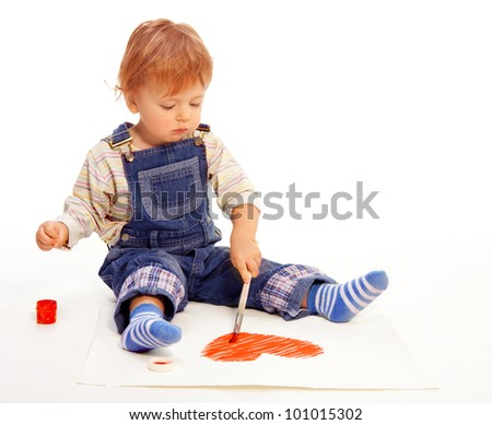 Cute little boy painting a heart shape on the paper before Valentine day