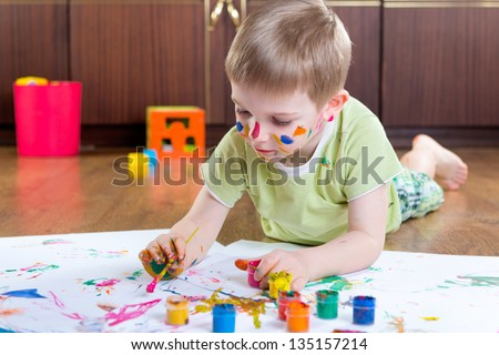 Cute little boy painting with colorful paints