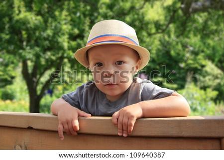 Cute little boy, peeking over a fence. - stock photo