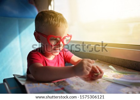 Cute little boy planning his economy vacations during travelling time by train, transport, happy family vacation and summertime, lifestyle inside portrait