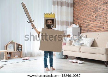 Cute little boy playing cardboard armor in living room Stock photo ©