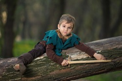 Cute little boy playing in the woods dressed as a knight with sword