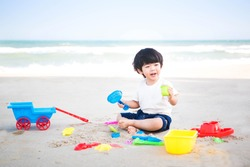 Cute little boy playing sand at the beach with sand tools.