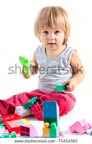 Cute little boy playing with blocks, isolated on white background
