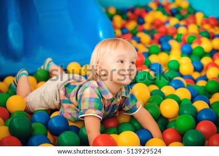 Cute little boy playing with toys on playground in the kindergarten.